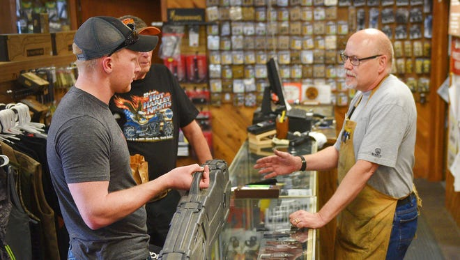 Alex Lerdal, left, talks to gun smith Steve Hansen at Garry's Gun Shop Friday. Lerdal already owns different guns. He has been deployed with the U.S. Navy for the past 3 years and wanted to update his guns now that he is home.