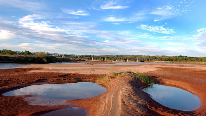 Two mirror-smooth pools of water stand in sharp contrast to the red clay surrounding them off the main channel of the Red River.
