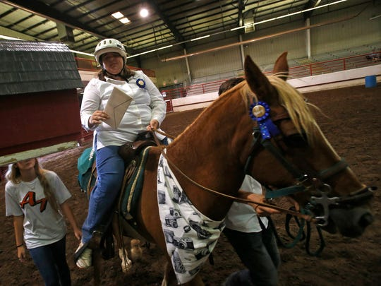 Mariah Hurd prepares to place a letter in a mailbox while riding Savvy on Wednesday during a San Juan County Fair equestrian show for people with special needs in Memorial Coliseum at McGee Park in Farmington.