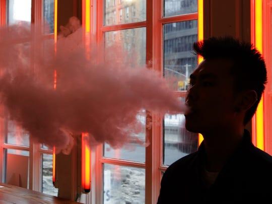 A patron exhales vapor from an e-cigarette at the Henley