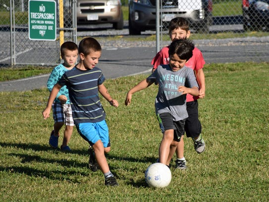 A group of boys kick a soccer ball around on the sidelines