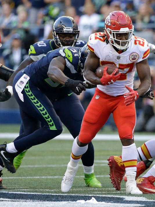 Kansas City Chiefs running back Kareem Hunt (27) carries the ball as Seattle Seahawks strong safety Kam Chancellor reaches for the tackle during the first half of an NFL football preseason game, Friday, Aug. 25, 2017, in Seattle. (AP Photo/Elaine Thompson)