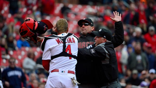 Cardinals catcher Yadier Molina takes exception to  what Diamondbacks manager Torey Lovullo says to the umpire.