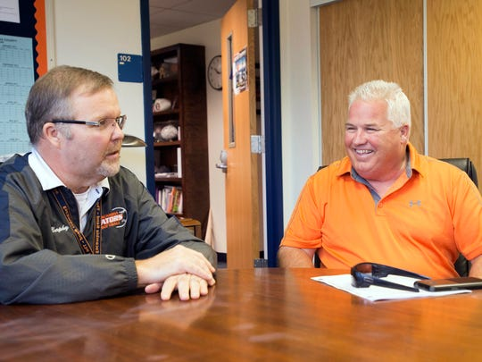 Escambia High School principal, Frank Murphy, left, and new head football coach, Mike Bennett, right, swap game day stories with each other Friday morning.