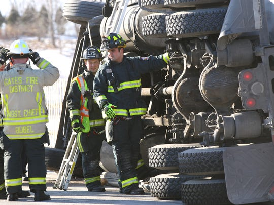 Gates firefighters work on scene after a tractor-trailer overturned on Harek Road, the exit off Route 531 into Rochester Technology Park in Gates.