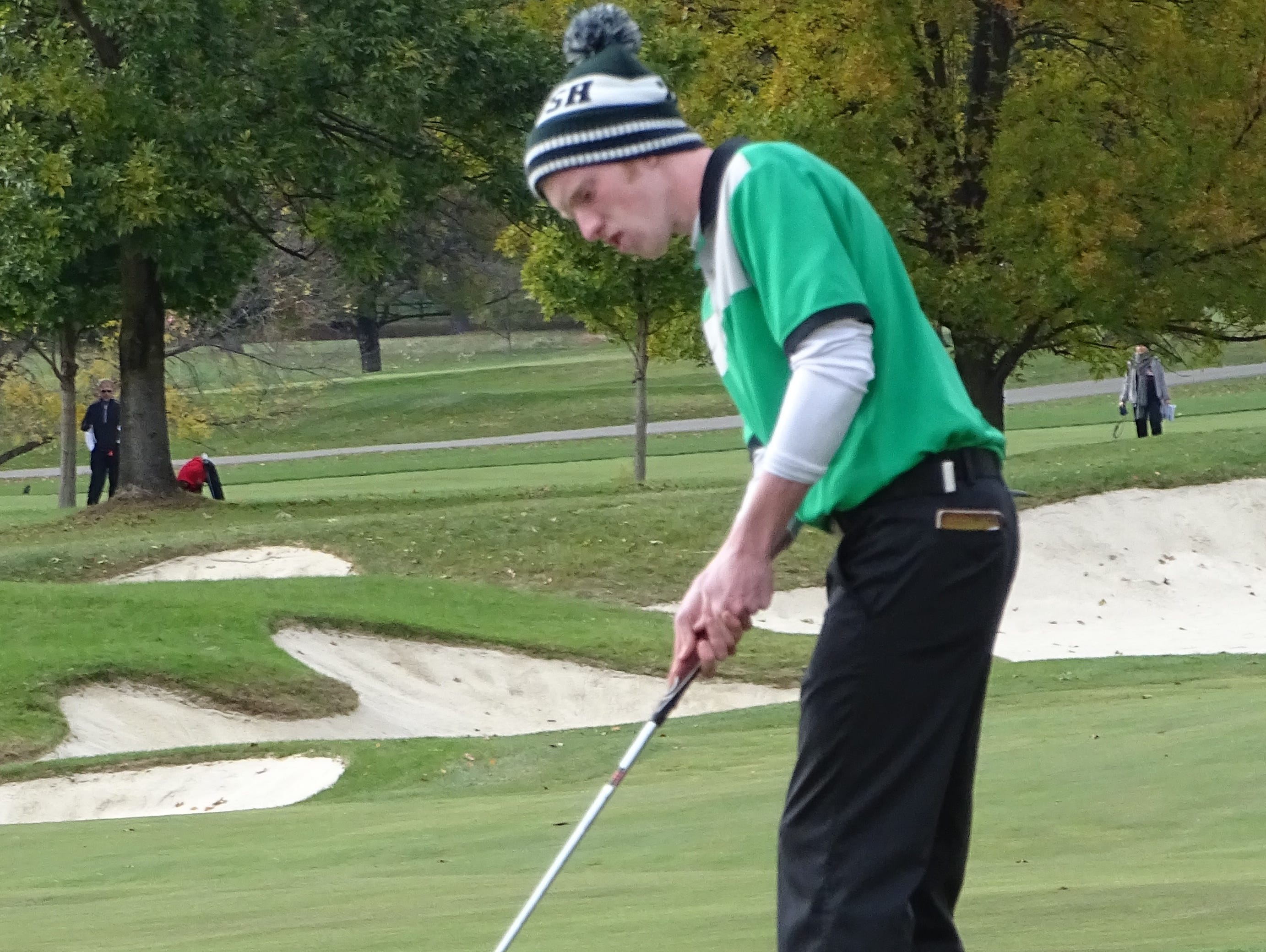 Fisher Catholic senior Aaron Wood putts on the 18th green at Ohio State's Scarlet Course. The Irish won the Division III state championship.