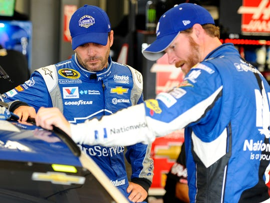 Jimmie Johnson (left) talks with Hendrick Motorsports teammate Dale Earnhardt Jr. during practice for the Quaker State 400 at Kentucky Speedway.
