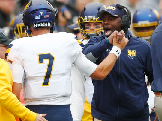 Northern Colorado head coach Earnest Collins, Jr., right, congratulates quarterback Jacob Knipp after he tossed a touchdown pass to wide receiver Alex Wesley against Colorado in the first half of an NCAA college football Saturday, Sept. 16, 2017, in Boulder, Colo. (AP Photo/David Zalubowski)