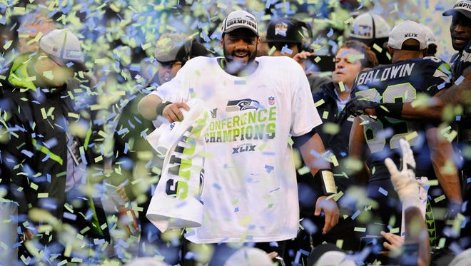 Seattle Seahawks quarterback Russell Wilson celebrates as the confetti pours onto the field following their victory over the Green Bay Packers in the NFC Championship Game at CenturyLink Field.