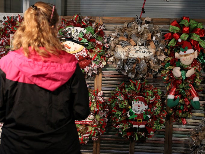 A shopper looks through a booth selling decorated wreaths