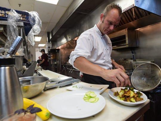Executive chef Matt Smith garnishes a dish.