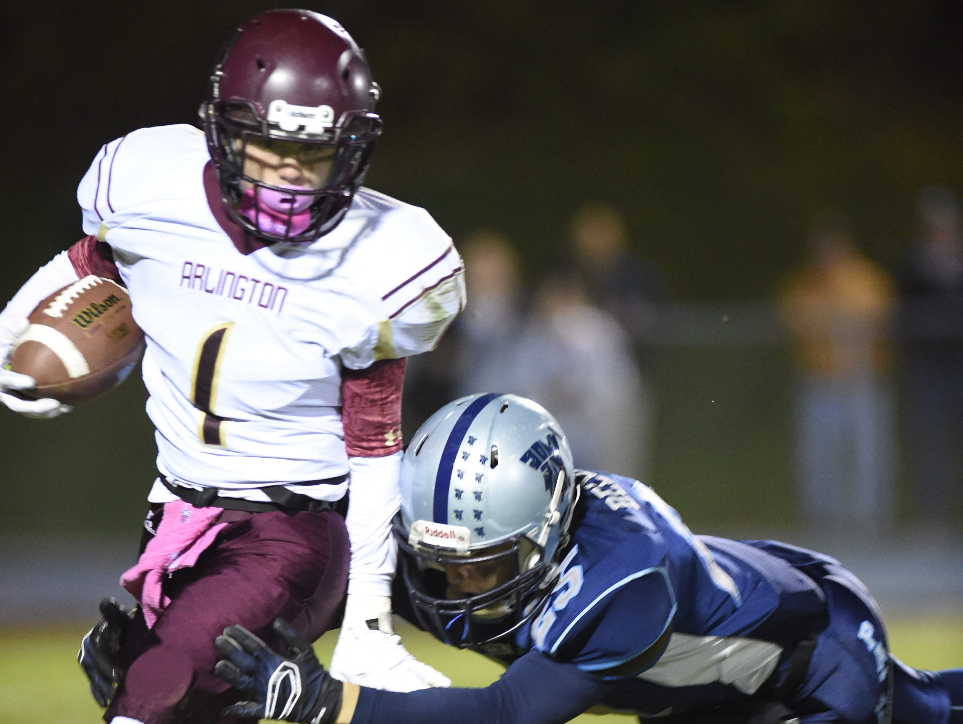 Arlington's Anthony Lantern gets tackled by John Jay's Todd Belotti during Friday's game in Wiccopee.