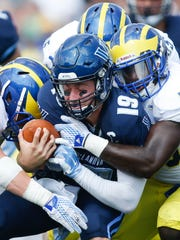 Delaware's Charles Bell (left) and Larry Spears (43) wrap up quarterback John Robertson at Villanova Stadium in 2015.
