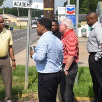 Opelousas Mayor Reggie Tatum, left, discusses road conditions in Opelousas with Rep. Dustin Miller Friday at the intersection of Landry and Academy Streets in downtown Opelousas.