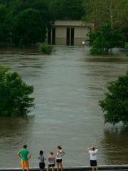 People climb on top of a building on campus in June 2008 to look out across the Iowa River at the flooded University of Iowa Museum of Art.