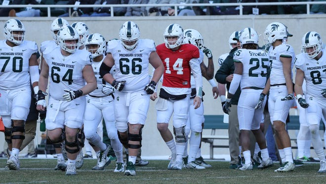 Michigan State quarterback Brian Lewerke (14) leads the offense onto the field during the annual spring game Saturday, April 7, 2018 at Spartan Stadium.