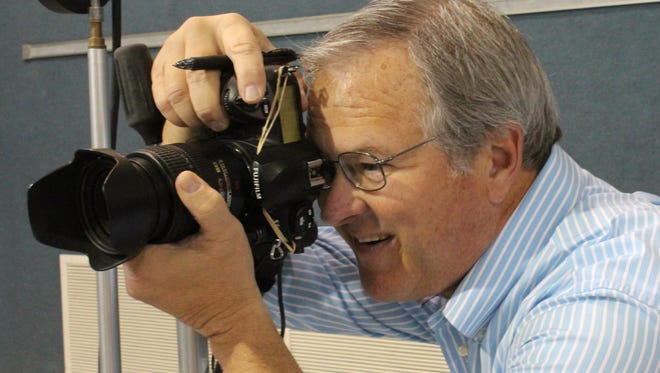 Wayne Henington takes a photo of a fifth-grader at Reagan Elementary. Before he takes a photograph, he makes sure the student is turned properly to the camera and may lighten the moment to draw a smile.