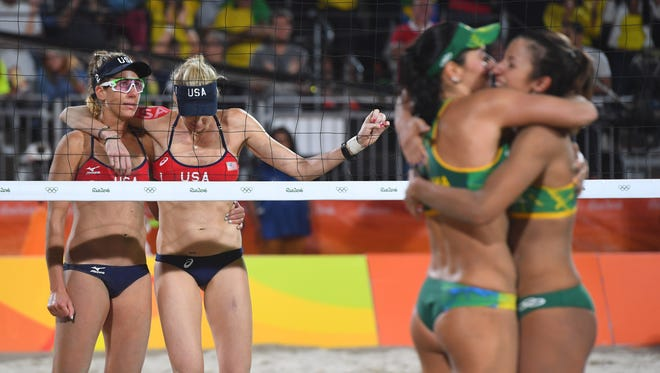 April Ross and right blocker Kerri Walsh Jennings look on at left as Brazil's Agatha and Barbara celebrate their victory.