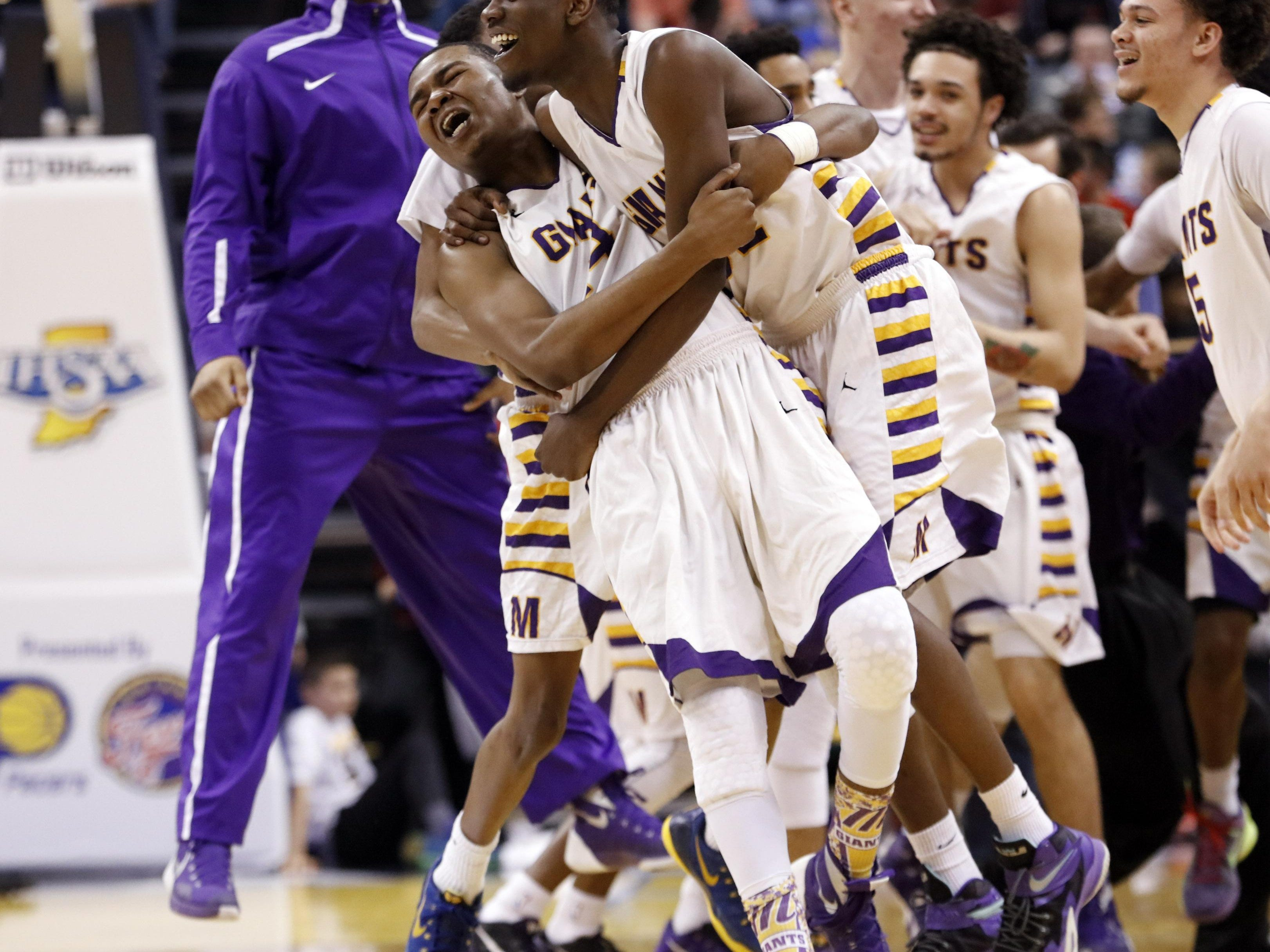 Marion's Jordan Smith, left, and Juswon White celebrate after defeating Evansville Bosse in the Indiana Class 3A IHSAA state championship basketball game in Indianapolis, Saturday, March 26, 2016. Marion won 73-68. (AP Photo/AJ Mast)