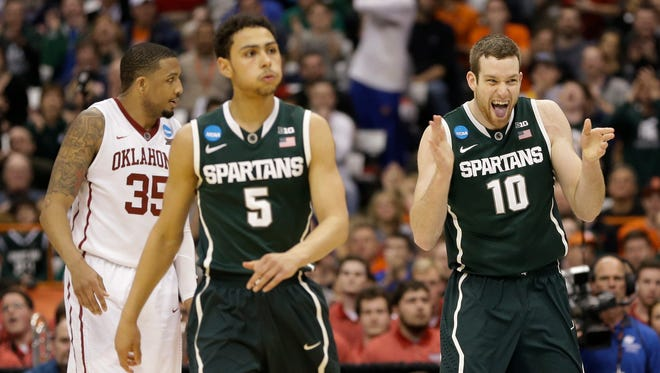 Michigan State's Matt Costello (10) and Bryn Forbes (5) react as Oklahoma's TaShawn Thomas looks away during the second half of a regional semifinal in the NCAA tournament Friday, March 27, 2015, in Syracuse, N.Y.