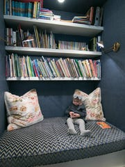 Penny Laakso, 2-year-old granddaughter of homeowners Karl and Eva Helminen, gets ready to read in a book nook Thursday, Nov. 30, 2017.