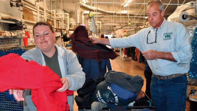 Bart Byars of Evergreen Cleaners sorts through coats to be cleaned.