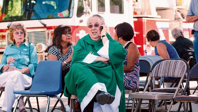 While waiting in a staging area on Aug. 2, 2015, Holy Cross Catholic Church Monsignor John Anderson tries to get in touch with other local churches to warn them of two explosions that occurred at Las Cruces churches that morning.