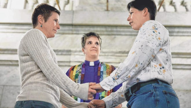 April Dawn Breeden, left, and her longtime partner Crystal Peairs are married by the Rev. Katie Hotze-Wilton on Wednesday at City Hall in St. Louis.