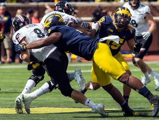 Cincinnati quarterback Hayden Moore is hit by Michigan