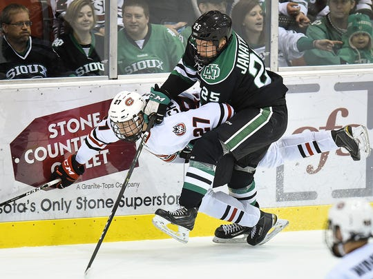 St. Cloud State's Dennis Cholowski is checked off the puck and into the boards by University of North Dakota's Joel Janatuinen on Nov. 19, at the Herb Brooks National Hockey Center.