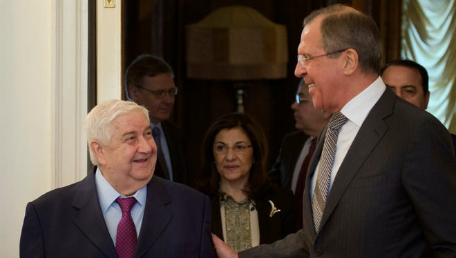 Russian Foreign Minister Sergey Lavrov, right, welcomes Syrian Foreign Minister Walid Moualem in Moscow on Monday.