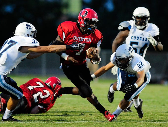 Centennial players Trent McDemott (37) and Peyton Pisacane (22) try to catch Overton's Ugo Amadi (7) during a game at Overton on Aug. 29, 2014.