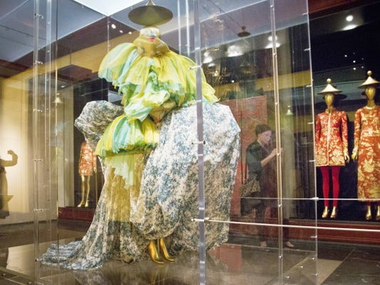 """A 2003 haute couture ensemble from designer John Galliano, left, shares space with a 1996-97 Karl Lagerfeld designed dress and evening gown pair, right, on display during the press preview for the Metropolitan Museum's Costume Institute exhibition """"China: Through the Looking Glass,""""  Monday, May 4, 2015, in New York."""
