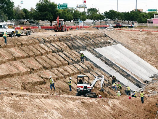 Workers install concrete walls to a stormwater ponding area being constructed on Wednesday by the El Paso Water Utilities along the 3200 block of Gateway Boulevard East at Estrella Street south of Interstate 10 in Central El Paso.