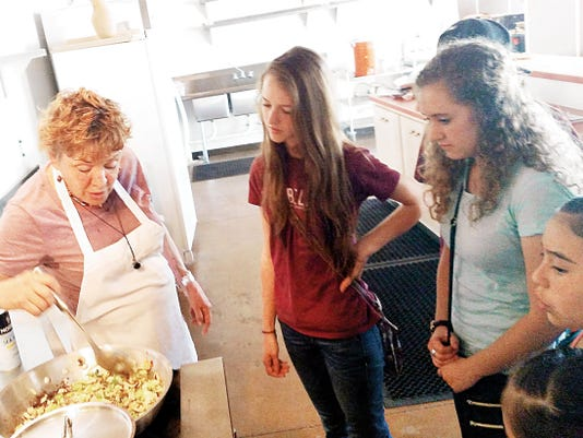 Diane Barrett demonstrates caramelizing to gathered youth. Barrett is co-owner of DianeþÄôs Restaurant and Bakery. She shared her recipe with local youth during 101 Things For Youth To Do In Grant County, which is offering free cooking demonstrations to youth every Thursday this summer at The Volunteer Center. From left to right: Diane Barrett, Sinea Runnels, Zachery Diaz (in hat behind), Emily Zollinger, and Xolymar Franco.