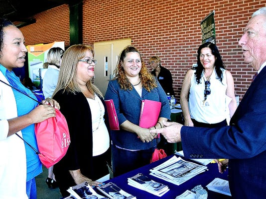 From left, Marta Morales, Margarita Olivo Torres, Delia De Jesus, all of York City, with Walkyria Sessions, of Community Progress Council Inc., talk with recruiting specialist Pedro Gratacos, right, of State Civil Service Commission about career possibilities during York Career Fair Monday at Santander Stadium.