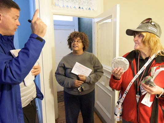 Red Cross volunteer Michael Smith of Big Brothers Big Sisters and Red Cross worker Edna Reinard talk about fire safety with Vilisha Barnes, center, after their crew installed a smoke detector in her West King Street home Thursday, Oct. 15, 2015.