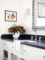 In this photo provided by Burnham Design, striped drawer and door pulls neatly echo the chevron-patterned mirror in this residential bathroom.