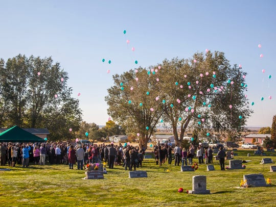 Family and friends release balloons during the funeral