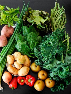 Roughly clockwise, from bottom left: Green onions, sweet potatoes, basil, green lettuce, green beans, kale, Asian pears, bell peppers, onion, potatoes and spinach. Photo by Chris Dunn.