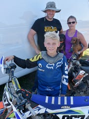 Motocross racer Logan Lockwood, with pit crew, dad Jason Lockwood, mom Marcey Lockwood, holding Hunter and Meela.