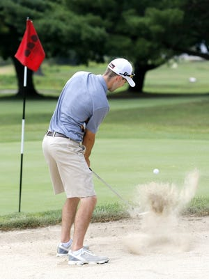 Rick Olson chips from the sand trap at the 16th green during Friday's first round of the Twin Tiers Golf Championship at Willowcreek Golf Course in Big Flats.