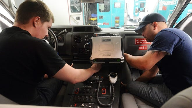 Robb Price and Nick Eberhardt install cabling for the computerized dispatch services in one of the new ambulances May 15 at Paramedics Plus.
