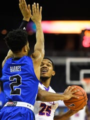University of Evansville's Duane Gibson (25) looks to shoot over defense from Indiana State's Jordan Barnes (2) as the University's of Evansville Purple Aces play the Indiana State Sycamores at the Ford Center Wednesday, January 17, 2018.