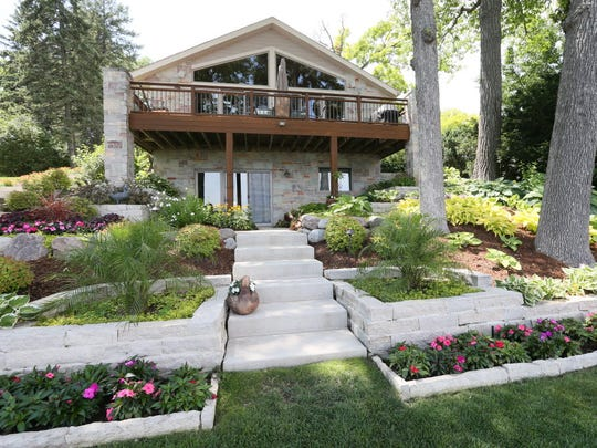 Landscaping and flowers surround the lake side of the Delafield home of Jeff and Laura Otto in 2016.