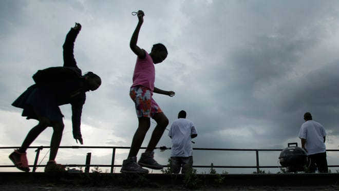 Nine-year-old Detroit cousins A'Janae Wallace and Mia Wright balance themselves on old railroad tracks along the waterfront in Detroit while they wait for the fireworks to begin. Their families barbecue and fish along the Detroit River, Monday, June 22, 2015.