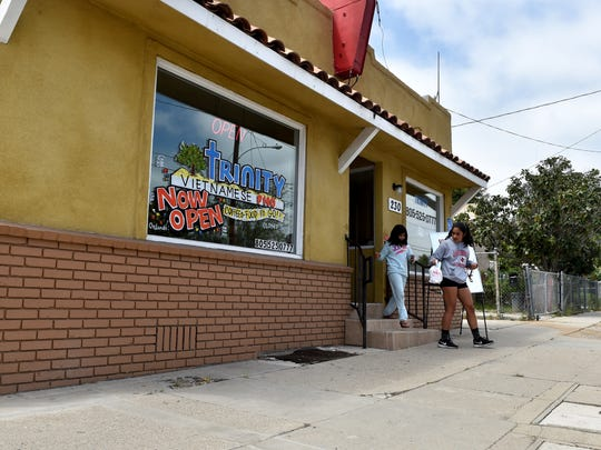 Vician Cruz (right), 17, and Maya Martinez, 11, carry out their lunch order at Trinity Coffee and Food in Santa Paula.