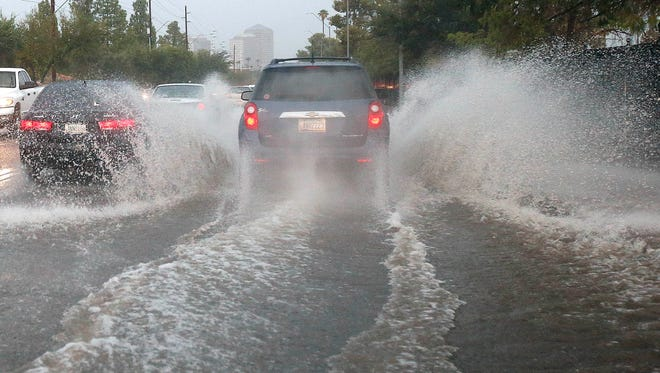 Drivers navigate through a flooded street as heavy rains and severe thunderstorms move through the metro Phoenix area on Sept. 27.