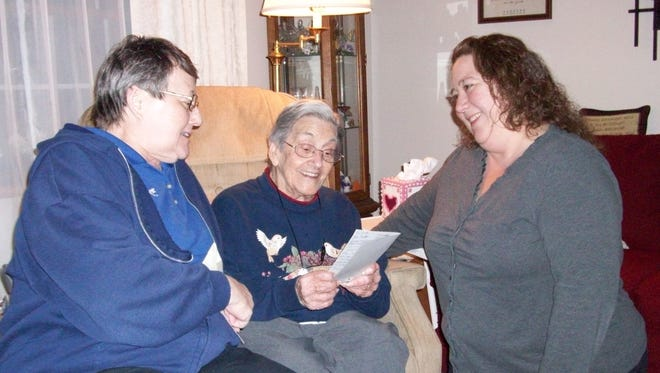 Mother-daughter pair Jeannie and Jennifer Kohler deliver a Valentine's Day Card Feb. 9 with Nora Lee Orr.