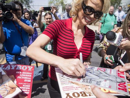 PETA spokeswoman Pamela Anderson signs her autograph